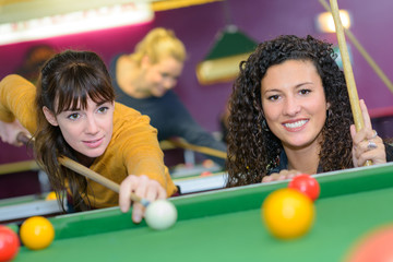 Two women playing pool