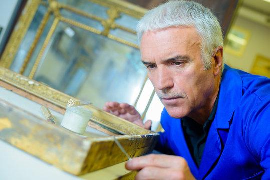 Mature man repairing frame