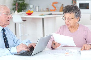 elderly lady dictating letter for husband to type on laptop