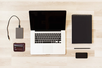 Flat lay home office workspace with laptop, diary, pencil, phone, purse and hard drive, on wooden background. Flat lay, top view. Minimal style.