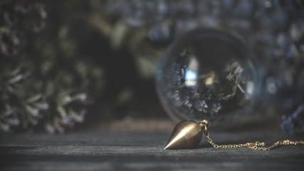 Pendel vor einer Kristallkugel, in der sich getrocknete Heil- und Räucherkräuter spiegeln.