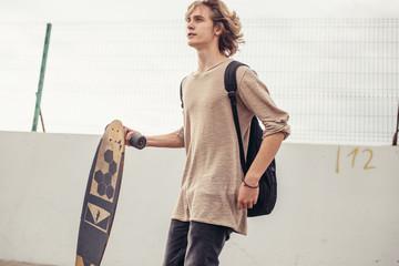 young curly male longboarder walking outside with longboard in hands
