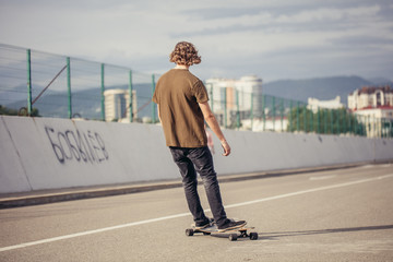 young boy riding longboard on boardwalk, warm summer time