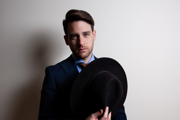 Portrait of a stylish handsome young man wear suit and holding a fedora hat in studio