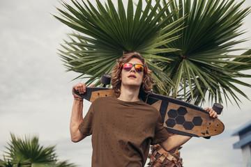 Handsome skateboarder wering sunglasses holds longboard on shoulder on city street or tropic background