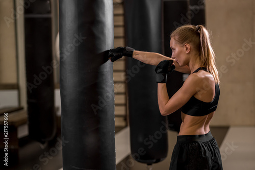 Attractive Athlete Blond Female With Earphones Punchin Bag Boxing Gloves In Gym