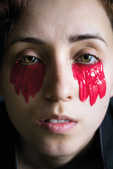 fashion close-up portrait of a girl in black clothes with red paint under the eyes