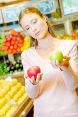 Lady holding red apple in one hand and a green apple in the other