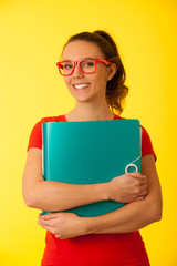 Young happy excited geek woman in red t shirt over vibrant yellow background