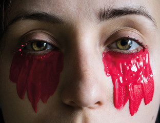 photo fashion close-up of female eyes of green color with red paint under them