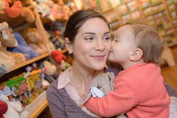 young mother her daughter shopping at the toy store