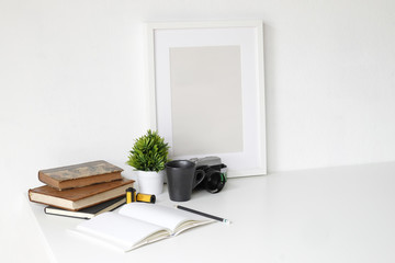 Work table with photography camera, book, notepad and pencil on white table and empty photo frame.