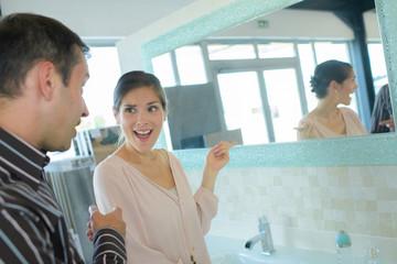 happy couple choosing tile for bathroom in store