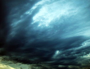 Dark storm clouds in the sky.  The sun comes out of the clouds. Dramatic background. Stormy weather.