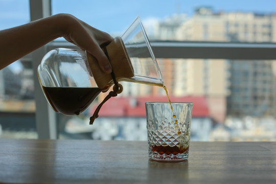 contrast picture, female graceful hand is pouring coffee from glass jar into glass, near window