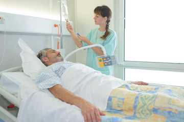 Nurse checking patient's drip