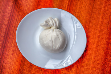 Burrata, typical Southern Italian soft cheese filled with butter, in a plate with wood background