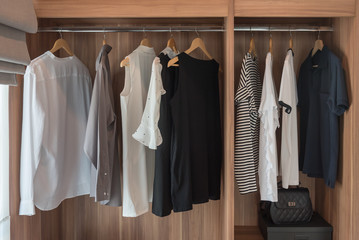 modern walk in closet with clothes