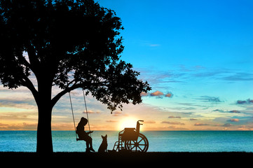 Girl schoolgirl invalid sitting on a swing under a tree by the sea, reading a book, beside a wheelchair and her dog