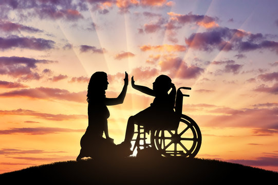 Happy disabled child girl in wheelchair and her mom on a walk
