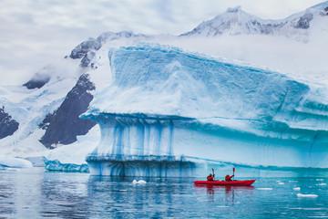winter kayaking in Antarctica, extreme sport adventure, people paddling on kayak near iceberg