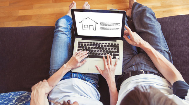 young family couple choosing new home online, search real estate to buy or rent, house for sale on screen of computer