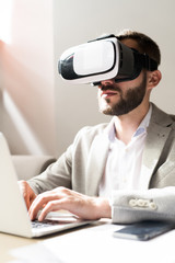 Serious concentrated bearded businessman in VR goggles managing device on laptop at office