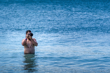 Tourist in the water taking pictures