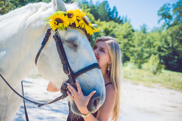 Nice lady at countryside with white horse. A beautiful rider and horse. Artistic Photography at horse farm. Attractive woman riding on horse rural location