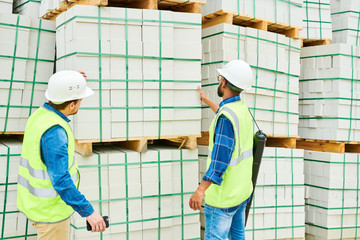 Back view of two men in helmets and waistcoats looking at stack of building materials during inspection on construction site
