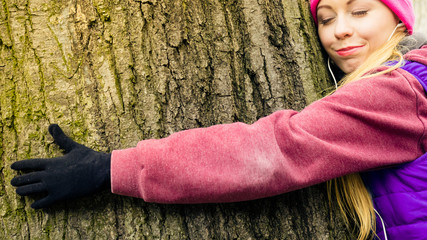 Woman wearing sportswear hugging tree