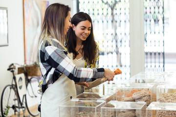 Beautiful young woman customer choosing spaghetti sold by weight in organic shop.