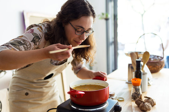 Beautiful woman tasting the food while cooking in an organic store.
