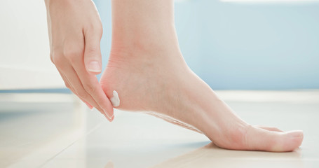 woman apply cream with foot