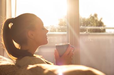 Girl enjoying morning coffee in living room