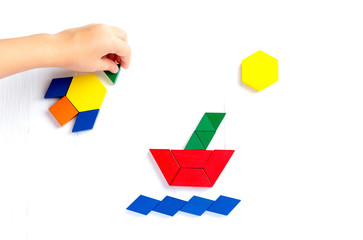 The ship sails on the sea waves, the sun shines brightly. Summer happy atmosphere. A child plays with colored blocks constructs a model on a light wooden background.