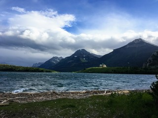 the shoreline of waterton lake on a windy summer's day with the Prince of Wales Hotel sitting on the point