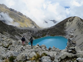 Andes Mountains, Cusco, Peru - May 7th, 2016.  A young peruvian tour guide and Canada hiker admire a beautiful lake nestled high in the Andes Mountains along the Salkantay Trail.