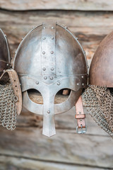 Replica of a medieval warrior Viking helmets on the wooden wall background.