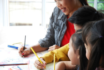 Teachers are teaching drawing on white paper to three children in holiday weekend. Background blur