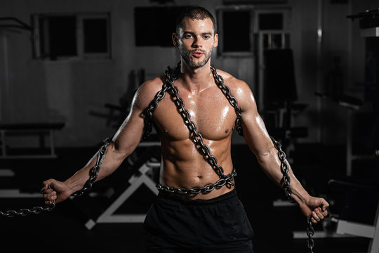 Muscular man slave in chains in gym, the prisoner