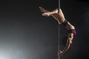 Obraz Beautiful slim girl with pylon. Female pole dancer dancing on a black background - fototapety do salonu