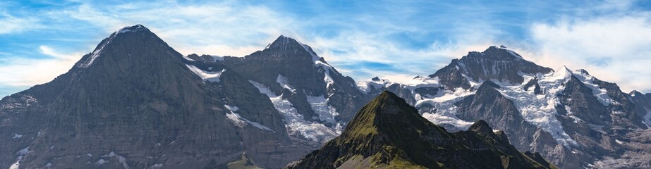 A beautiful panoramic view on Eiger north face, Monch and Jungfrau seen from Mannlichen (in the foreground) in the summer. High resolution image. Bernese Alps - Switzerland.