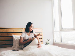 Woman play ukulele on her bed in the morning.