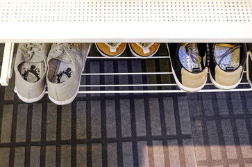 Sports shoes on a stand in the hallway.