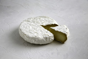 Ripe tasty cheese camembert or brie on a cracked table