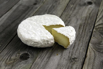 Ripe tasty cheese camembert or brie on an old plank table