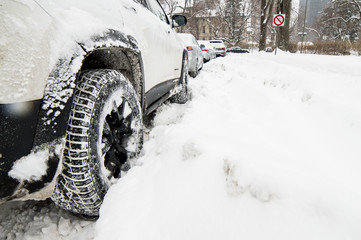 Low angle view of car stuck in deep snow conceptual snow storm and winter weather safety photography