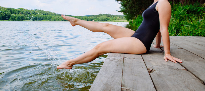 young pretty woman sitting on wooden dock legs in water