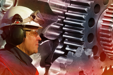 worker, engineer examining large gears and cog machinery, production steel heat of red flames